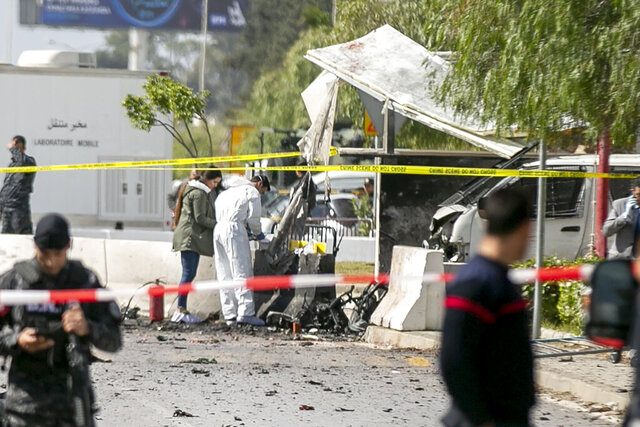 Forensic officers work on a blast site near the US Embassy in Tunis, Friday, March 6, 2020. Tunisian media are reporting that two people on a motorcycle have set off a blast near the U.S. Embassy in the capital Tunis, the private Radio Mosaique said that five police officers were wounded and described it as a suicide attack. (AP Photo/Riadh Dridi)
