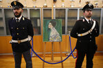 An Italian Policeman, left, and a Carabiniere, paramilitary police officer, stand beside a painting which was found last December near an art gallery and believed to be the missing Gustav Klimt's painting 'Portrait of a Lady' during a press conference in Piacenza, Italy, Friday, Jan. 17, 2020. Art experts have confirmed that a stolen painting discovered hidden inside an Italian art gallery's walls is Gustav Klimt's