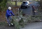 Megan Whitmore of Post Falls, Idaho,  pulls branches from a fallen tree with help from her neighbor Ed Macdonald Wednesday, Jan 13, 2021.  A powerful wind storm has rolled through the Pacific Northwest  leaving a trail of damage.  (Kathy Plonka/The Spokesman-Review via AP)