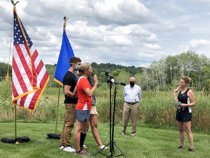 Wisconsin Supreme Court Justice Jill Karofsky is sworn in by fellow Justice Rebecca Dallet, right, as her children, Danny and Daphne, and former Gov. Jim Doyle look on. Karofsky took the oath Saturday, Aug. 1, 2020, in Basco, Wis., during a break in a 100-mile run. (Patrick Marley/Milwaukee Journal-Sentinel via AP)