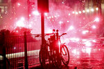 Flares illuminates the road as clashes broke out during a protest against the government restriction measures to curb the spread of COVID-19 in Turin, Italy, Monday, Oct. 26, 2020. Italy's leader has imposed at least a month of new restrictions to fight rising coronavirus infections, shutting down gyms, pools and movie theaters and putting an early curfew on cafes and restaurants. (Claudio Furlan/LaPresse via AP)