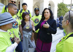 Assemblywoman Lorena Gonzalez, D-San Diego, second from right, talks with members of Rideshare Drivers United, who support her measure to limit when companies can label workers as independent contractors, which was approved by a Senate committee, in Sacramento, Calif., Wednesday, July 10, 2019. Her bill, AB5, aimed at major employers like Uber and Lyft, still needs approval by the full Senate. (AP Photo/Rich Pedroncelli)