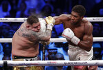 FILE - In this early Sunday Dec. 8, 2019, file photo, defending champion Andy Ruiz Jr., left, takes a right cross to the face during his fight against Britain's Anthony Joshua in their World Heavyweight Championship contest at the Diriyah Arena, Riyadh, Saudi Arabia. (AP Photo/Hassan Ammar, File)