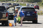 A boy gets help putting on a backpack at the parking lot to Good Harbor Beach in Gloucester, Mass., Friday, May 22, 2020. Cars in the lot were parked spaced apart due to social distancing rules. Beaches in Gloucester reopened with restrictions on Friday after being closed two months ago due to the pandemic. (AP Photo/Charles Krupa)
