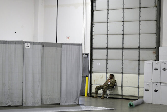 A member of the National Guard sits in a field medical station in the Meadowlands Exposition Center in Secaucus, N.J., Thursday, April 2, 2020. New Jersey Gov. Phil Murphy toured the 250 room medical station that is expected to open early next week. It is slated to field non-coronavirus cases. It's one of four such facilities that are supposed to open in New Jersey. (AP Photo/Seth Wenig)