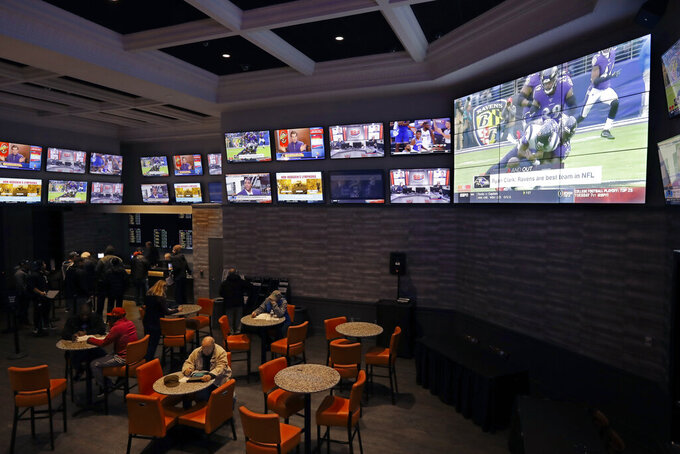In this Nov. 18, 2019, photo, patrons visit the sports betting area of Twin River Casino in Lincoln, R.I. Legalized sports betting's rapid march across the U.S. could face some bigger tests in 2020. Less than two years after a U.S. Supreme Court ruling opened the door to sportsbooks outside Nevada, they have been legalized in states that are home to about one-third of the nation's population. (AP Photo/Steven Senne)