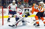 Washington Capitals' Braden Holtby kicks away a shot by Philadelphia Flyers' Oskar Lindblom during the second period of an NHL hockey game Thursday, March 14, 2019, in Philadelphia. (AP Photo/Tom Mihalek)