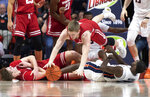 Wisconsin guard Brevin Pritzl (1) dives over forward Nate Reuvers (35) and Illinois guard Da'Monte Williams (20) for a loose ball during the second half of an NCAA college basketball game in Champaign, Ill., Wednesday, Jan. 23, 2019. (AP Photo/Stephen Haas)