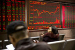 Chinese investors monitor stock prices at a brokerage house in Beijing, Wednesday, March 20, 2019. Markets in Asia are mostly lower after a lackluster day of trading on Wall Street. (AP Photo/Mark Schiefelbein)