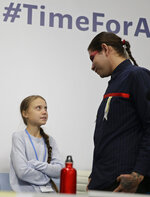 Climate activist Greta Thunberg, left, speaks with another young activist at the COP25 Climate summit in Madrid, Spain, Monday, Dec. 9, 2019. Thunberg is in Madrid where a global U.N. sponsored climate change conference is taking place. (AP Photo/Andrea Comas)