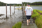 Bart White, front, and Jeff White, owners of SeaTow Lower Chesapeake, walks out to the family pier where a SeaTow boat is moored on Tuesday, June 22, 2021, in Seaford, Va. In 2003, when Bart saw an advertisement in the Daily Press for a boat-towing company, it made sense to buy it. The White family have run SeaTow Lower Chesapeake from their homes in Seaford, where they have lived as watermen for four generations making a living off of the Chesapeake Bay. (Trent Sprague/The Virginian-Pilot via AP)