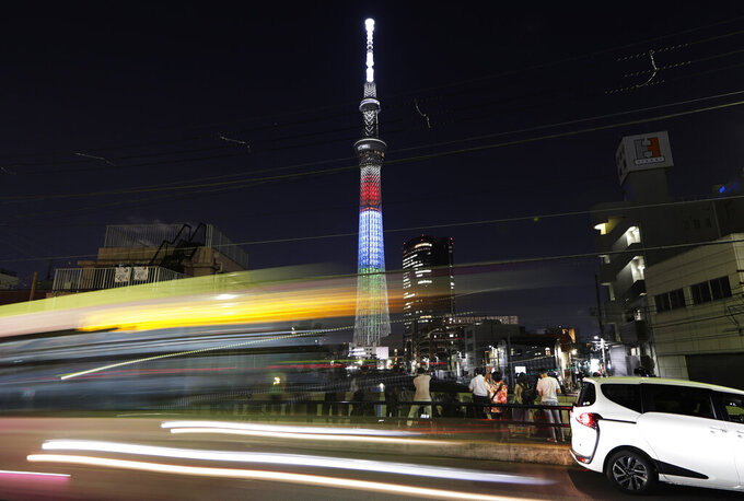 During a long exposure catching a streak of light from passing cars, journalists report on the special lighting of the Tokyo Skytree in red, blue and green; the symbol colors of the Tokyo 2020 Paralympic Games, in Tokyo on Monday, Aug. 24, 2020. The lighting Monday marked one year to go before the planned opening of the Paralympics that was postponed due the the coronavirus pandemic. (AP Photo/Hiro Komae)
