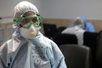 FILE - In this March 8, 2020 file photo, a nurse wears protective gear in a ward dedicated for people infected with the new coronavirus, at a hospital in Tehran, Iran. While crippling sanctions imposed by the U.S. government left the country ill-equipped to deal with the fast-moving virus, some medical professionals say government and religious leaders bear the brunt of the blame for allowing the virus to spread -- and for hiding how much it had spread. (AP Photo/Mohammad Ghadamali, File)