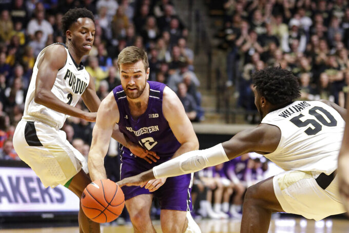 Northwestern guard Pat Spencer (12) drives between Purdue guard Eric Hunter Jr. (2) and forward Trevion Williams (50) during the first half of an NCAA college basketball game in West Lafayette, Ind., Sunday, Dec. 8, 2019. (AP Photo/Michael Conroy)
