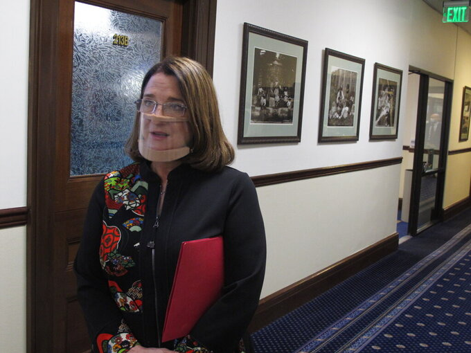 Alaska state Sen. Lora Reinbold, an Eagle River Republican, speaks to reporters on Monday, March 15, 2021, in Juneau, Alaska. Reinbold returned to her seat on the Senate floor Monday with a new face-covering meant to comply with COVID-19 mitigation policies after Senate leaders last week took action to restrict her access to the floor and committee hearings for what they said were policy violations. (AP Photo/Becky Bohrer, Pool)