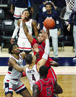 Connecticut guard Tyrese Martin (4) shoots against St. John's guard Julian Champagnie (2) in the second half of an NCAA college basketball game in Storrs, Conn., Monday, Jan. 18, 2021.  (David Butler II/Pool Photo via AP)