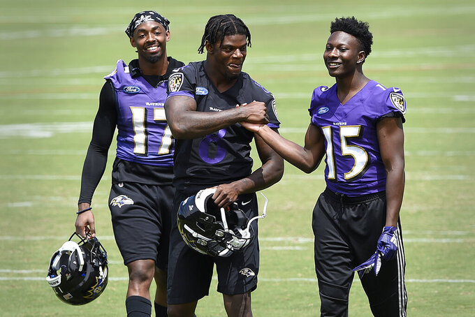 Baltimore Ravens quarterback Lamar Jackson, center, shakes hands with Marquise Brown after workouts at the team's NFL football training facility in Owings Mills, Md., Wednesday, June 12, 2019 (AP Photo/Gail Burton)