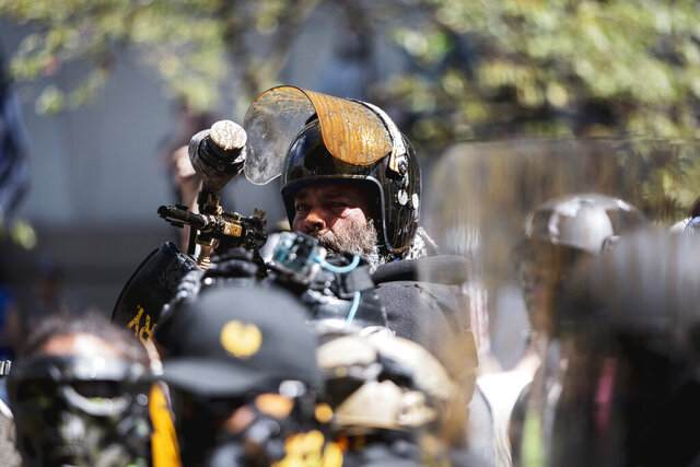 Alan Swinney points a paintball gun at a group of counterprotesters, Saturday, Aug. 22, 2020, in Portland, Ore. Far-right organizers with the stated goal of