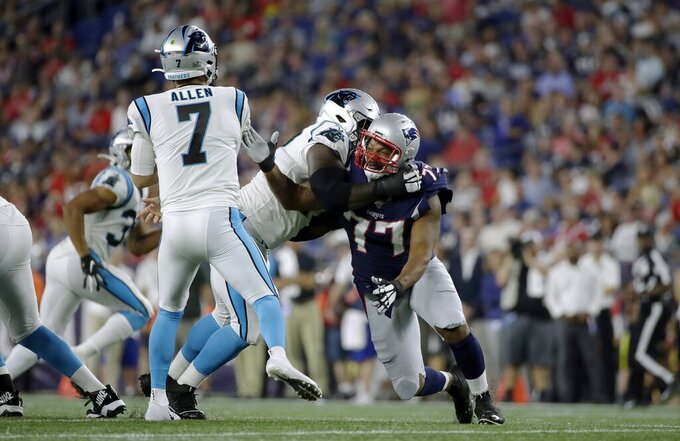 New England Patriots defensive end Michael Bennett (77) tries to fight through a block by Carolina Panthers offensive tackle Taylor Moton as he pressures Panthers quarterback Kyle Allen (7) in the first half of an NFL preseason football game, Thursday, Aug. 22, 2019, in Foxborough, Mass. (AP Photo/Elise Amendola)