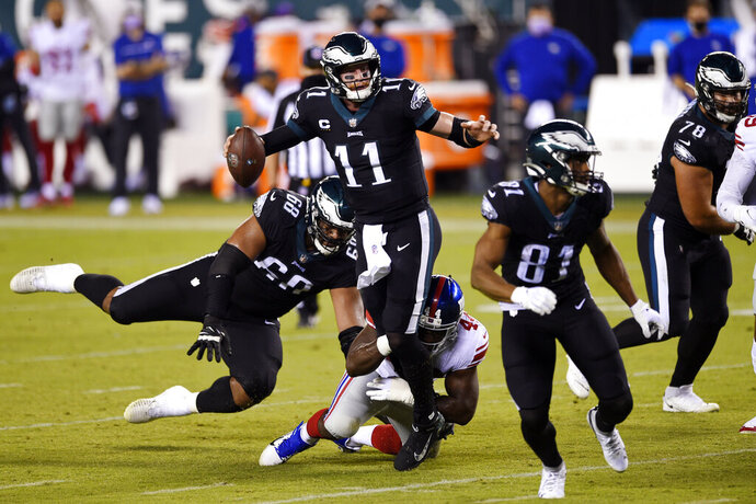 Philadelphia Eagles' Carson Wentz (11) is grabbed by New York Giants' Markus Golden (44) during the first half of an NFL football game, Thursday, Oct. 22, 2020, in Philadelphia. (AP Photo/Derik Hamilton)