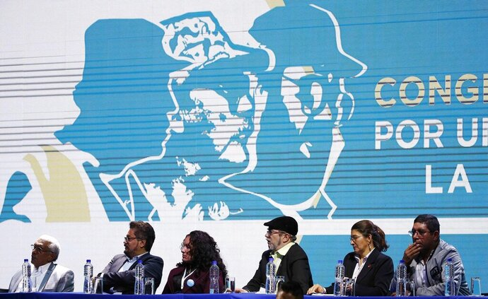 CORRECTS DATE - FILE - In this Aug. 27, 2017 file photo, leaders of the Revolutionary Armed Forces of Colombia (FARC), sit before former guerrillas as they lead the FARC's National Congress where they launched their political party in Bogota, Colombia. The top peace negotiator for the FARC announced Thursday, Aug. 29, 2019, that he and a cadre of hardline supporters are taking up arms again, accusing President Ivan Duque of failing to uphold the accord that sought to end a half century of bloody fighting. (AP Photo/Fernando Vergara, File)