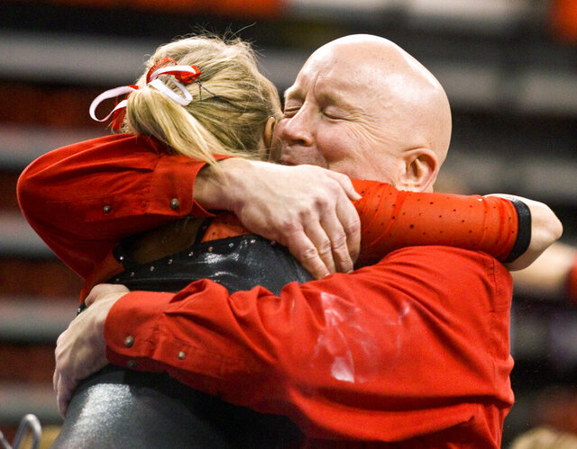 FLE - In this March 4, 2012, file phto, Nebraska head coach Dan Kendig embraces Janelle Giblin after she competed in the uneven parallel bars during an NCAA college gymnastics meet against Florida in Lincoln, Neb. The Nebraska women's gymnastics program has been placed on two years' probation and fined for breaking NCAA rules under former head coach Dan Kendig. The Division I Committee on Infractions announced Tuesday, April 28, 2020, the program exceeded the number of allowable coaches when Kendig and members of the program arranged for a former volunteer coach to receive impermissible compensation from 2014-18. (Patrick Breen/Lincoln Journal Star via AP, File)