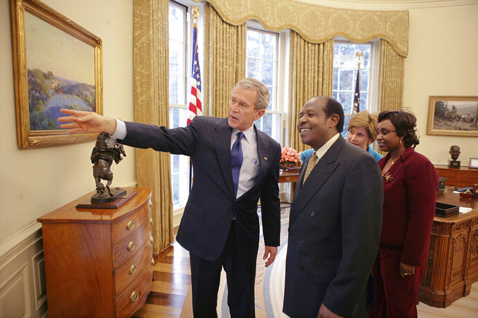 FILE - In this Thursday, Feb. 17, 2005 file photo provided by the White House, President Bush, left, and first lady Laura Bush, 2nd right, meet with Paul Rusesabagina and his wife Tatiana in the Oval Office. Rusesabagina, who inspired the film