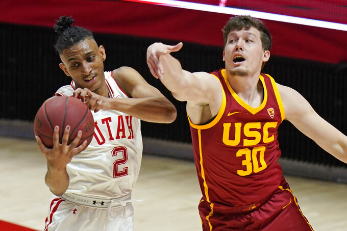 Utah guard Ian Martinez (2) pulls down a rebound as Southern California guard Noah Baumann (30) defends during the first half of an NCAA college basketball game Saturday, Feb. 27, 2021, in Salt Lake City. (AP Photo/Rick Bowmer)