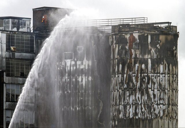 St. Bernard firefighters battle a 3-alarm fire after silos caught fire at the century-old Domino Sugar Refinery in Arabi, La., Thursday, Aug. 27, 2020. (David Grunfeld/The Times-Picayune/The New Orleans Advocate via AP)