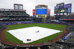 Workers remove water from the tarp before changing it out before a baseball game between the New York Mets and the Atlanta Braves was postponed due to rain, Sunday, May 30, 2021, in New York. (AP Photo/Kathy Willens)