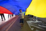 A boy plays under a Venezuelan national flag during a protest against new sanctions by the administration of US President Donald Trump that affect the Venezuelan state airline CONVIASA, in Caracas, Venezuela, Monday, Feb. 10, 2020. US Treasury Secretary Steven T. Mnuchin said in a statement last Friday that Maduro's
