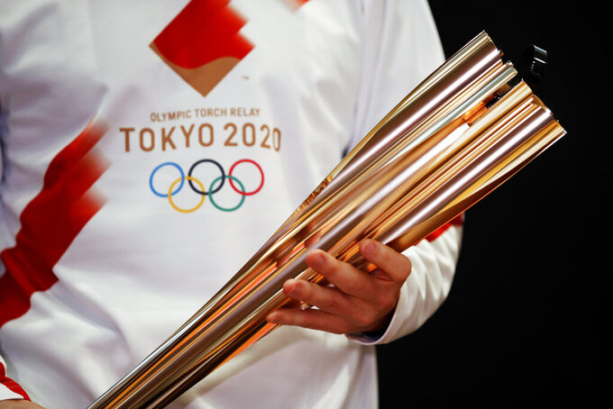 FILE - In this Feb. 24, 2020, file photo, Greek singer Sakis Rouvas wears the uniform of the torch relay runners in Athens, Greece, as he holds the torch of the 2020 Tokyo Olympic Games during a presentation of the torch relay within in Greece. A governor in a western Japanese prefecture is talking about canceling the torch relay events in his area for the Tokyo Olympics, Kyodo News reported Wednesday, Feb. 17, 2021.  (AP Photo/Thanassis Stavrakis)