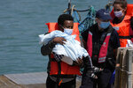 A man and a child thought to be migrants are disembarked from a British border force vessel in Dover, south east England, Thursday, July 22, 2021. The number of undocumented migrants reaching Britain in small boats this year has surpassed the total for all of 2020, as people smugglers take advantage of good weather to cross the English Channel from France. (AP Photo/Matt Dunham)