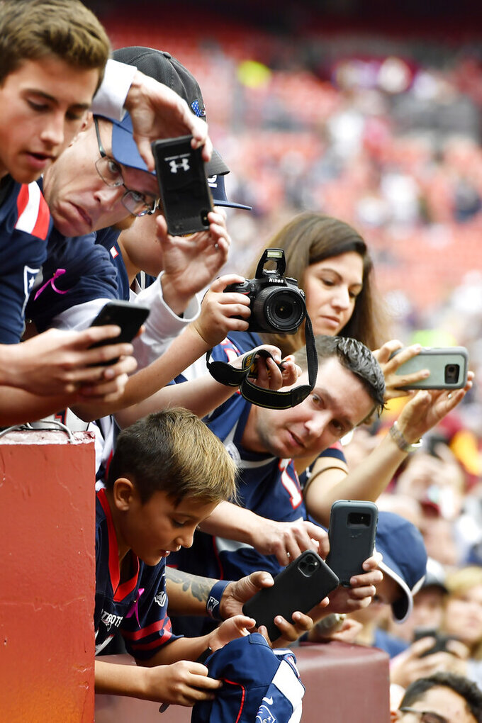New England Patriots fans wait for the team ahead an NFL football game between the Washington Redskins and the New England Patriots, Sunday, Oct. 6, 2019, in Washington. (AP Photo/Mike Stewart)