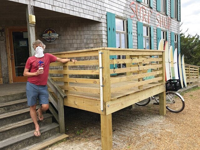 Bob Chestnut stands outside of his Ride the Wind Surf Shop on North Carolina's Ocracoke Island on June 25, 2020. The secluded travel destination was ravaged by Hurricane Dorian in September and then hit with coronavirus-related travel restrictions in the spring. Residents and business owners are hoping to recoup some of their losses as tourists return, albeit in smaller than usual numbers. But they're wary of a possibly busy hurricane season ahead. (AP Photo/Ben Finley)