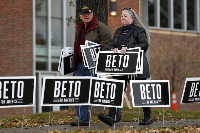 Supporters for Democratic presidential candidate Beto O'Rourke carry signs while waiting for him to speak before the Iowa Democratic Party's Liberty and Justice Celebration, Friday, Nov. 1, 2019, in Des Moines, Iowa. O'Rourke told his supporters that he was ending his presidential campaign. (AP Photo/Charlie Neibergall)