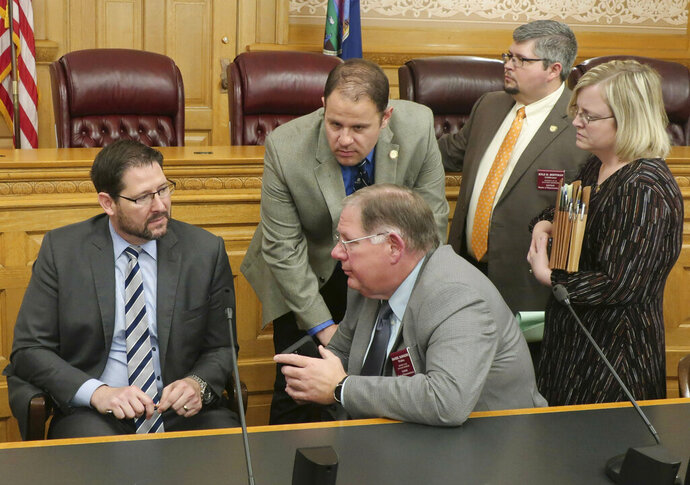 Kansas House Speaker Ron Ryckman Jr., left confers with fellow House members and staffers before an unsuccessful attempt to revive an anti-abortion bill vetoed by Democratic Gov. Laura Kelly, Thursday, May 2, 2019, at the Statehouse in Topeka, Kansas. Conferring with Ryckman are, House Majority Leader Dan Hawkins, R-Wichita, center seated, Melinda Gaul, Ryckman's communications director, right, Rep. Kyle Hoffman, R-Coldwater, second from right, and B.J. Harden, Hawkins' chief of staff. (AP Photo/John Hanna)