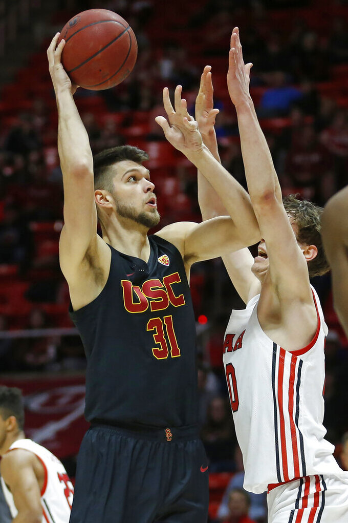 Utah forward Mikael Jantunen, right, defends as USC forward Nick Rakocevic (31) shoots in the first half of an NCAA college basketball game Sunday, Feb. 23, 2020, in Salt Lake City. (AP Photo/Rick Bowmer)