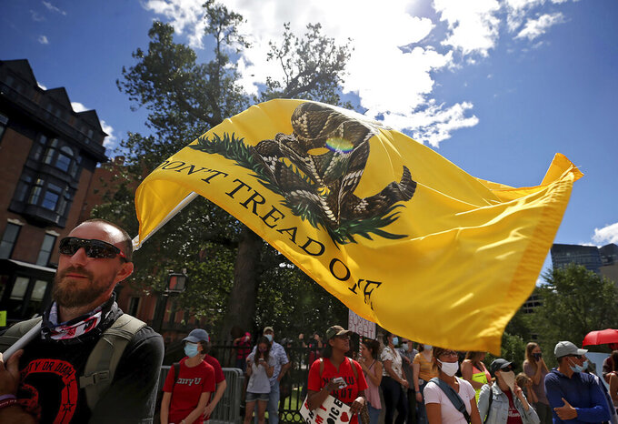 """Sean Courtney, of West Springfield, holds a """"Don't Tread on Me,"""" flag during a protest against mandatory flu vaccinations, outside the Massachusetts State House, Sunday, Aug. 30, 2020, in Boston. Public health authorities say flu shots are very important this year to avoid overburdening the health system. amid the coronavirus pandemic. (Nancy Lane/Boston Herald via AP)"""