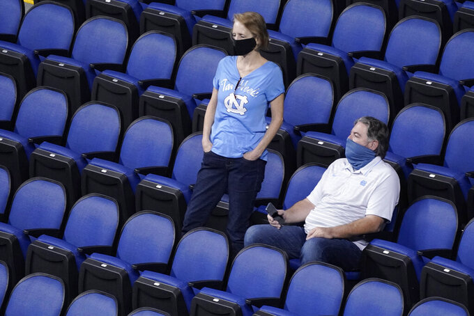 Basketball fans watch the action between Syracuse and North Carolina State during the second half of an NCAA college basketball game in the second round of the Atlantic Coast Conference tournament in Greensboro, N.C., Wednesday, March 10, 2021. (AP Photo/Gerry Broome)