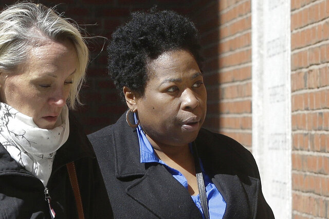 FILE - In this March 25, 2019, file photo, former college entrance exam administrator Niki Williams of Houston, right, arrives at federal court in Boston to face charges in a nationwide college admissions bribery scandal. Williams is scheduled to be sentenced on Monday, Dec. 21, 2020, after pleading guilty in September. (AP Photo/Steven Senne, File)
