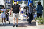 People wear masks while walking on Sunset Blvd, Thursday, July 2, 2020, in West Hollywood, Calif. Sheriff's deputies in West Hollywood will issue citations to people who are not wearing masks in public, ramping up enforcement that previously had largely been imposed without penalties. (AP Photo/Ashley Landis)