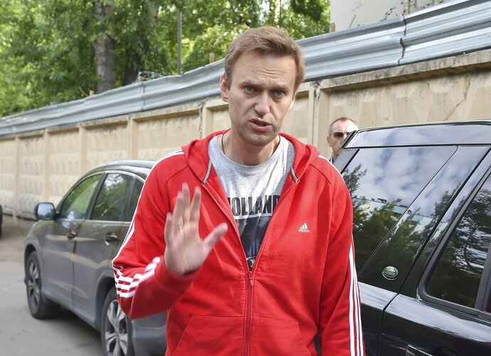 Russian opposition activist Alexei Navalny greets colleagues as he leaves a detention center in Moscow, Russia, Thursday, June 14, 2018.  Russian opposition leader Alexei Navalny has been released from custody after serving a 30-day jail sentence for staging an unsanctioned protest in Moscow. (AP Photo/Dmitry Serebryakov)