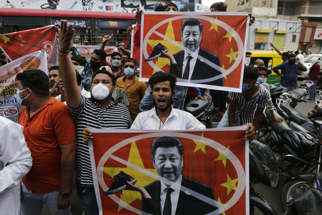 Karni Sena supporters hold banners featuring Chinese President Xi Jinping and shout slogans during a protest against China in Ahmedabad, India, Wednesday, June 24, 2020. Chinese and Indian military commanders have agreed to disengage their forces in a disputed area of the Himalayas following a clash that left at least 20 soldiers dead, both countries said Tuesday. The commanders reached the agreement Monday in their first meeting since the June 15 confrontation, the countries said. (AP Photo/Ajit Solanki)