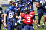 Seattle Seahawks quarterback Russell Wilson (3) bumps fists with tight end Colby Parkinson Sunday, Aug. 30, 2020, during an NFL football training camp in Renton, Wash. (AP Photo/Elaine Thompson)