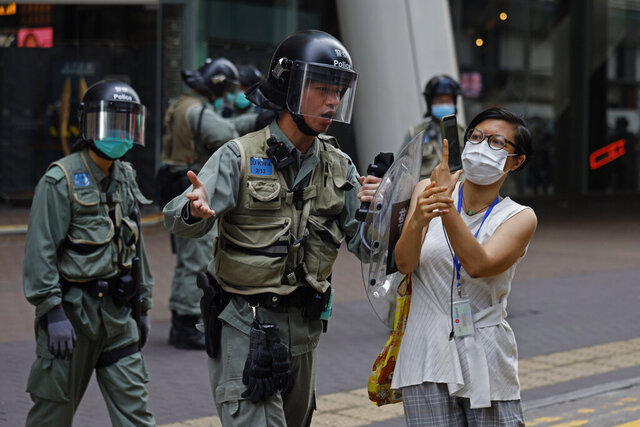 Riot policeman pushes a woman as she is taking a photograph of the detained protesters at the area in Mongkok, Hong Kong, Wednesday, May 27, 2020.  U.S. Secretary of State of Mike Pompeo has notified Congress that the Trump administration no longer regards Hong Kong as autonomous from mainland China. (AP Photo/Kin Cheung)