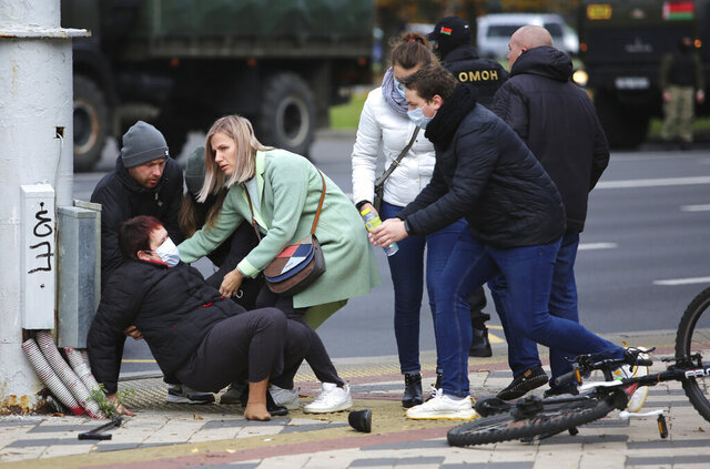 People help a woman after she collided with a police during an opposition rally to protest the official presidential election results in Minsk, Belarus, Sunday, Nov. 1, 2020. Nearly three months after Belarus' authoritarian president's re-election to a sixth term in a vote widely seen as rigged, the continuing rallies have cast an unprecedented challenge to his 26-year rule. (AP Photo)