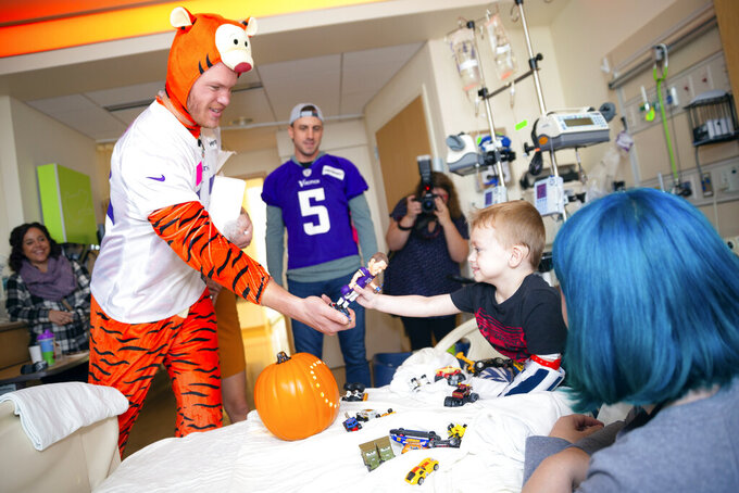 In this Oct. 30, 2018 photo provided by the NFL, Minnesota Vikings tight end Kyle Rudolph visits a young patient during the Vikings' Halloween Holiday Huddle at the University of Minnesota Masonic Children's Hospital in Minneapolis. (C. Morgan Engel/NFL via AP)