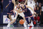 Gonzaga forward Drew Timme, left, fouls Saint Mary's guard Jordan Ford as they go after the ball during the first half of an NCAA college basketball game in Spokane, Wash., Saturday, Feb. 29, 2020. (AP Photo/Young Kwak)