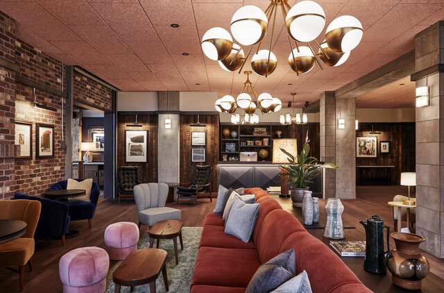 This photo shows the lobby in The Hoxton Hotel in Portland, Ore. London/L.A.-based Fettle designed Portland's Hoxton. Alongside newly-built rooms, public areas were situated in an old converted movie theater. Tailored but comfy mohair and leather seating and warm wood side tables blend with distressed rugs and displays of ceramics, plants and books. Refurbished timber and concrete beams frame the spaces. And there's a great story about the reception area's wood paneling.